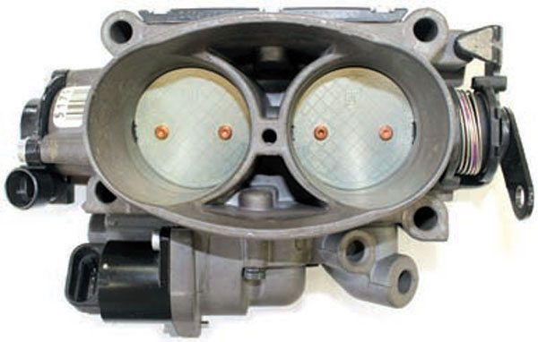 This Ram Jet 502 throttle body is essentially the same housing as the LT1 throttle body. Between the two 48-mm throttle openings and toward the bottom of the hourglass-shaped feature is a hole that mates to the IAC passage in the lower IAC housing. On the other side of the throttle blades is a passage that receives engine vacuum. When the IAC valve is closed, the engine vacuum cannot pull air through the IAC passage. As the PCM commands the IAC valve open, the engine receives additional air through the IAC passage. Notice the Ram Jet 502 lower IAC housing is not designed for coolant flow.