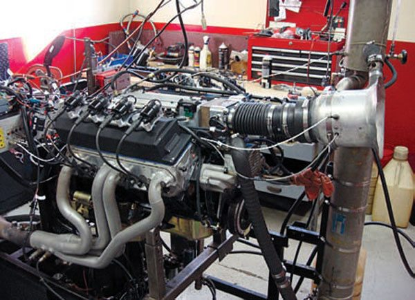 This engine dyno is used by TPIS to break in new engines, tune engine controllers, and test for maximum horsepower and torque. An engine dyno allows the tuner to operate an engine in a safe, controlled setting while making changes to the engine controller's calibration settings. By applying a load to the engine, the tuner can adjust calibration settings for operating conditions that are not possible without installing the engine into a vehicle and going for a drive.