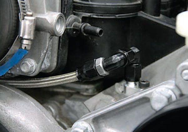 Using a couple of 90-degree fittings, the driver-side steam line runs under the throttle body to the passenger's side via braided Earl's line. (Photo Courtesy Blane Burnett)