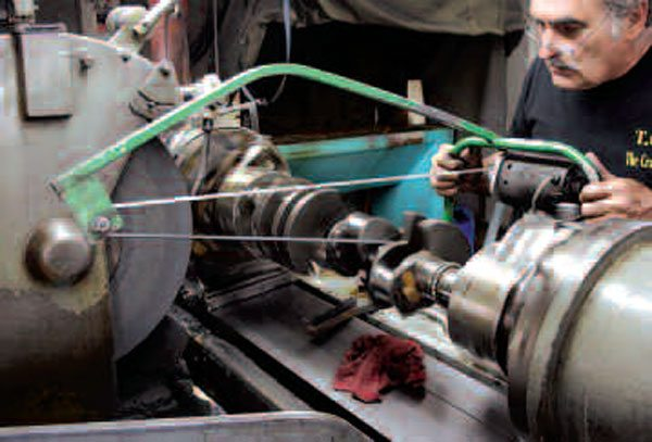 A typical crank journal polishing process involves spinning the crank in a special lathe while running three different polishing bands of varying coarseness over the journals. The result: super-smooth rod and main journals that will last many thousands of miles.
