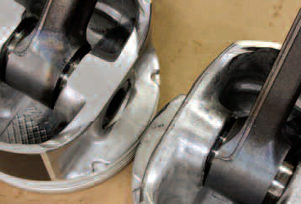 Before being pressed onto their rods, these pistons underwent the weight-matching process. The piston on the left was too heavy and needed to have material removed (look at the area below the piston pin) to match the one on the right, which was left alone. Good piston matching can be performed to within half a gram! Similar material removal on connecting rods is normally done with a grinding wheel or like tool.