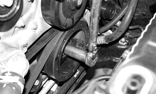 The first step in the procedure is removal of the 24-mm bolt holding the damper against the crankshaft hub. It is a very tightly torqued bolt that typically requires the leverage of a breaker bar to break it loose—and according to General Motors' engine assembly recommendations, the bolt should not be re-used. Because it is a torque-to-yield fastener, it should be replaced with a new bolt after removal.