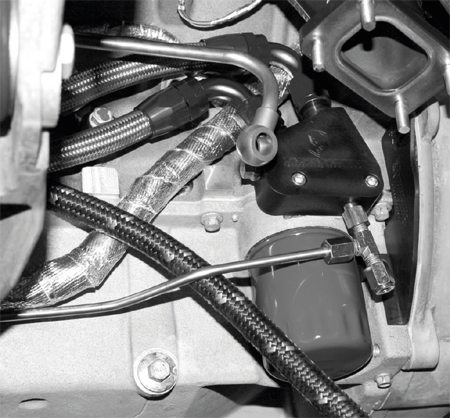 The hard oil-feed line wraps under the oil pan and up to a T-junction in an aftermarket oil cooler. The bottom fitting is reserved for the driver's-side turbo's oil-feed line.