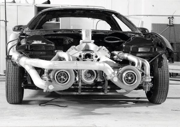 "The advantage of turbocharging in a racing application is clearly illustrated in this partially constructed fourth generation Firebird, as two very large turbochargers have been adapted to an LS engine. Except for the older, ""71""-series superchargers used in Top Fuel, Top Alcohol, and some Pro Mod-type drag racing classes, there aren't Roots and screw-type superchargers capable of delivering the airflow of a pair of extra-large turbos. Even large centrifugal blowers are typically limited to only one per engine. With a pair of turbos, each driven by half of the cylinders, the only real limit is keeping the engine itself together under maximum boost."