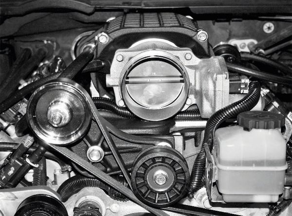 This photo shows the throttle body installed on the supercharger, as well as its lengthened wiring harness plugged into it. It also shows the myriad of other hoses, connectors, and fasteners re-attached to the engine and/or supercharger/manifold assembly. Despite their common LS engine architecture, different vehicles have different connections, sensors, and other hardware. Again, the manufacturer's assembly manual should be followed closely to ensure all of the connections have been made. A few items to check include the Idle Air Temperature (IAT) sensor, EVAP lines (which may require modification or replacement on some vehicles), purge solenoid, vacuum hoses, and MAP sensor/wiring harness.