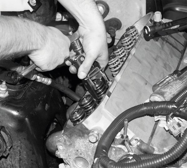 In the reverse of the process for removal, the compressed valve spring is slipped over the valvestem and seal. Then, the keeper and retainer are installed, and the spring compressor tool is backed off until the spring is held firmly in place.