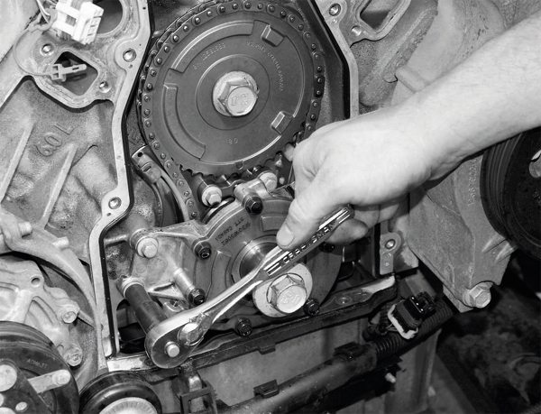 To remove the camshaft, you must first remove the oil pump and timing-chain set. The oil pump is the first to go, as seen here. Note the large, single bolt on the camshaft timing gear on this LS2 engine. Earlier LS engines were equipped with smaller, three-bolt fastening setups for holding the gear to the camshaft, but later engines were equipped with the large, single-bolt fastener. It is imperative to match the new camshaft and the timing gear, because they are not interchangeable.