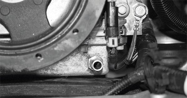 This photo shows the drilled and tapped oilreturn hole at the front of the oil pan on a C6 Corvette, at the lower corner of the driver's side. Other LS vehicles requiring a return hole have them in essentially the same place. The fitting for the return line has also been installed, using a liquid sealer in addition to the torque specifications for the fitting in the pan.