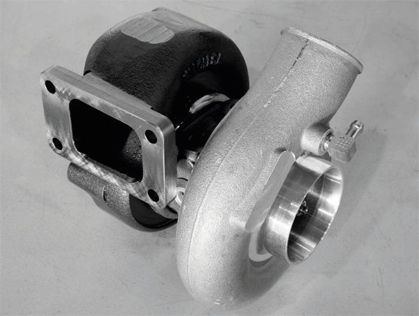 With this view of a basic turbocharger, it is easy to visualize its operation. Exhaust gas enters through the rectangular port on the left, which mounts on or near the exhaust manifold, and spins the turbine. When the turbine spins, it acts on a shaft that simultaneously spins the compressor on the opposite side of the unit. The spinning compressor draws in fresh air, compresses it and sends it as the boosted air charge into the engine.