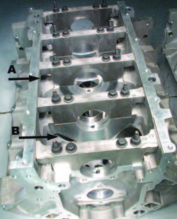 "The LS1 Beta engines showed that the engine would require some help to improve its bay-to-bay crankcase breathing. This was expected, but the ""windows"" that needed to be added were more substantial than expected. The early LS1s have a machined hole through all the main webs. Later, castin ports in the main webs (shown), introduced first on the LS6 and then on all Gen III engines, insure there was sufficient area for the oil vapor to move around in the bottom of the engine at high RPM."