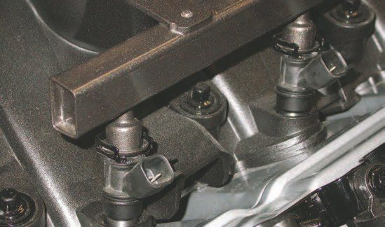 The low-profile Gen III car intake manifold takes in air from the front into an open area under ports that loop over the top of the open area and into the cylinder head intake ports. The intake and cylinder heads were designed from the beginning for a fuel-injection system. To take full advantage of the setup, the fuel injectors are located at the end of the intake manifold ports to shoot the fuel at the backside of the intake valve (shown).