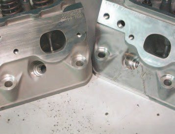 """If you are looking for used LS6 heads, the easiest way to identify them by a visual inspection is by the exhaust ports. The stock LS1 heads have oval exhaust ports, while the LS6 heads have """"D""""- shaped port exits. The head on the right with the """"triangle"""" casting mark is more desireable because it is the semi-permament mold casting — these consistently make 5-7 horsepower more than the sand cast head at the left."""
