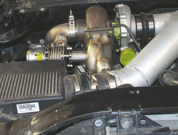 The W2W turbo kit is straightforward to install. The cast-iron exhaust manifolds are unbolted from the engine and flipped 180 degrees to position the outlets upwards and towards the front of the vehicle. The W2W tubing is then used to connect the turbo, intercooler, and inlet tract together. The total installation time is less than a day.