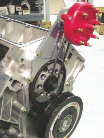 1. This clean setup is the result of the early machining work. The Jesel belt drive is fully installed, the distributor drive pulley is on the camshaft, and a belt connects the Jesel/Mallory distributor on the offset mount (built by W2W). Since the intake inlet is at the front of the engine on this intake, W2W had to build a special offset plate to work with the special offset intake inlet that places the throttle body off to the passenger side of the engine.