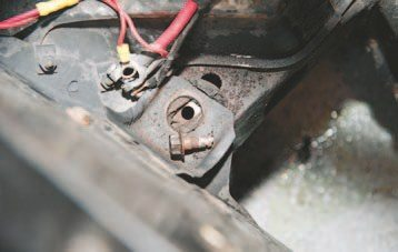 Two 1/2-inch bolts hold the core support to the front subframe. As you can see here, mine suffered under years of rust so it had to be cut out with a reciprocating saw. This is just one aspect of working on rusty old cars. Unfortunately, the massive body bolt was in a hard-to-reach location. The fastener lubricant didn't help budge the bolt and eventually I rounded off the head, leaving only one option: cut the bolt out.