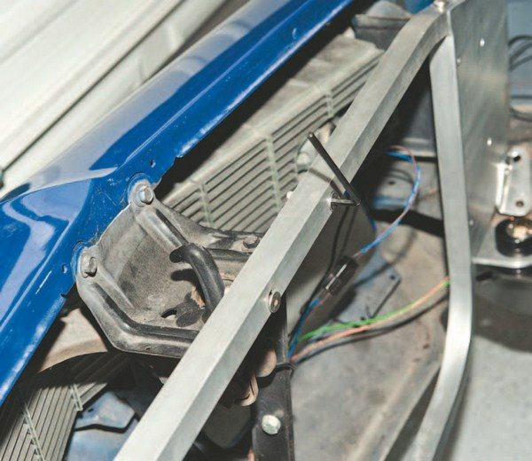 The new core support differs in size and the way it mounts to the front grille and latch support. A slot is on the inside of the core support; these two bolts need to thread through before you can attach the radiator. The new core support replaces the stock support and mounts in the exact same way using the stock bolt locations.