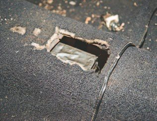 You will most likely have to cut a new access hole for the transmission shifter. So you measure it, mark it, and use a cut-off wheel to shorten it to the correct length. I tried to use the old hole, but as you can see, it's a bit off. Installing a fireproof shifter boot is a top priority. It's typically easier to remove the carpet before modifying the floor panel. I used a cutoff wheel on a grinder and a tin snip to make the final cuts.