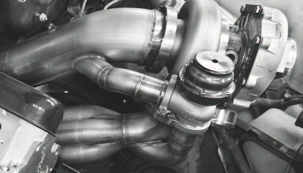 This photo clearly illustrates the elements of the turbo system and their relationship with one another. At the bottom of the system, the exhaust tubes from the exhaust header can be seen merging into the collector that mounts on the turbine side of the turbocharger. At the left of the system, the large-diameter tube is the down tube, which carries exhaust away after it spins the turbine. Also visible is a TiAL waste gate. Note how it is integrated with the down tube, as that's where the excess pressure is vented. Finally, the compressor side of the turbo is visible on the right-hand side of the photo, with the discharge end open. Tubing will be routing from it through an intercooler and on to the engine's throttle body.