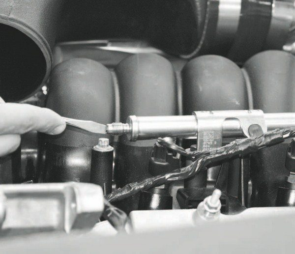 The tip of a flat-blade screwdriver is pressed on the Schrader valve to relieve pressure within the fuel lines. Care must be taken (including wearing eye protection) to prevent injury from the high-pressure spray of fuel that could occur. And, obviously, the procedure shouldn't be performed near heat sources or an open flame.