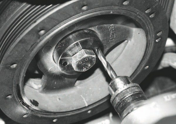 After the damper bolt is removed and the tool is installed, a drill is simply inserted through the template's hole(s) and driven into both the damper and crank hub.