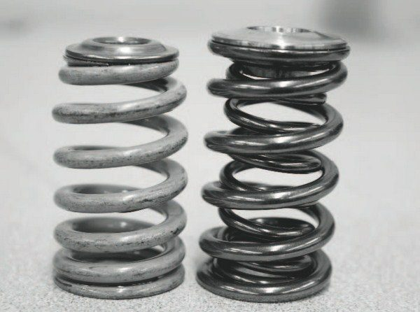A stock LS2 valve spring (left) is shown with a heavy-duty, higher-rate spring from Comp Cams (right). The stock spring has a single coil and a slight beehive shape. Note the smaller-width top compared to the Comp Cams spring. The replacement spring has a pair of inner and outer coils for exceptional strength. The stronger spring is not only necessary for standing up to the higher valve lift delivered by the new camshaft, but better withstands the cylinder pressure created by the blower or turbo.