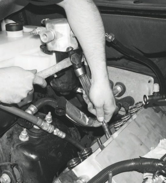 Prior to the new spring's installation, the new valvestem seal is slipped on. It is a tight fit that generally requires assistance to seat it all the way down onto the cylinder-head surface. In this case, a deep-well socket placed on top of the seal and a few gentle taps from a mallet or hammer does the trick.