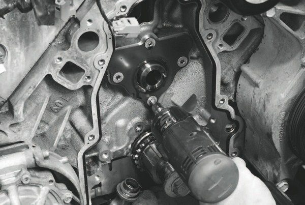 After the tensioner is removed, the camshaft retaining plate is unbolted and can be removed, too.