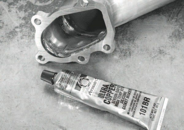 Although a metal gasket was used between the turbochargers and exhaust manifolds, the down pipes are mated to the turbos with Permatex Ultra Copper high-temperature silicone gasket maker. It is spread liberally on the mounting flange.