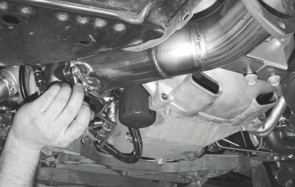 With the copper gasket maker on the flange, one of the down tubes is cinched down against the turbocharger. Note how both down tubes are further supported by mounting tabs that attach to the transmission bell housing.