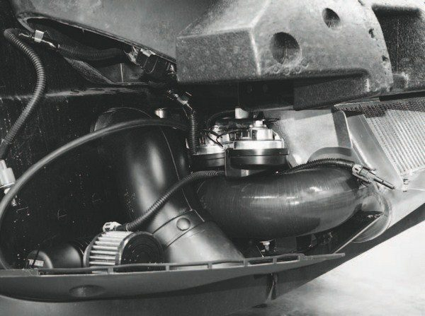 The bypass valve (lower left) for a centrifugal supercharger system mounted on a C6 Corvette is shown with the front fascia removed. When installed on a vehicle with a factorystyle mass airflow system, the bypass valve must be mounted between the intercooler outlet (flowing toward the engine) and before the mass airflow sensor. The intercooled air charge must only pass the mass airflow sensor once, or accurate air metering is impossible. That means bypass air shouldn't be introduced back into the intake stream ahead of the air meter; and bypass air released to the atmosphere shouldn't be vented after the air meter.