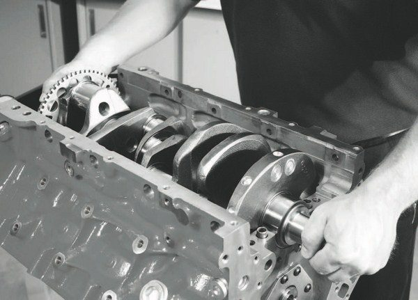 """A 4340-alloy steel forging is the strongest available for crankshafts, while traditional heat-treating methods such as nitriding and induction hardening can enhance strength. With nitriding, the crankshaft is placed in an oven and ionized nitrogen is vacuum deposited on its surfaces; a process that can double the surface hardness. Induction hardening, where the sections of the crankshaft are subjected to a magnetic field for intense heating and cooling, can produce a harder surface, but only where the process was applied. Nitriding treats the entire crankshaft at once. Another common """"trick"""" is knifeedging the crank's counterweights to reduce windage, but that has generally proven to be counter-effective to performance. The most efficient design is a rounded edge, as seen on the crankshaft being installed in this LSX block."""