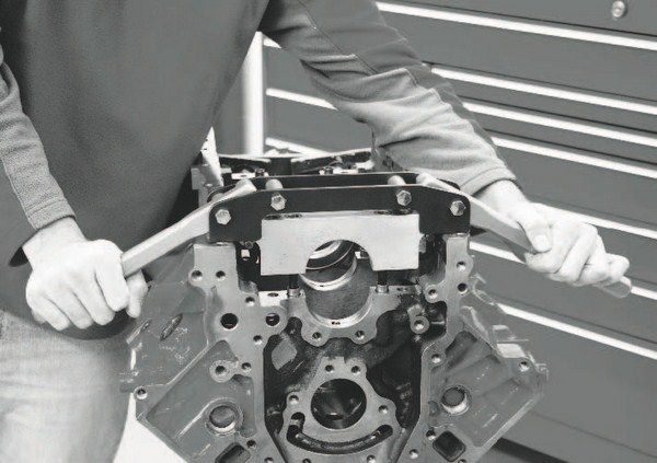 This is Thomson Automotive's LS main bearing removal tool, and it's pretty cool. The tight tolerance of the main bearing caps fitted to the longskirt LS-style cylinder block makes their removal difficult and time consuming. Thomson Automotive has come up with a simple, yet ingenious solution: a tool that hooks beneath the caps and uses the leverage of a pair of aluminum handles to yank the caps quickly and smoothly out of the block. Anyone who has struggled with removing LS main caps will appreciate this simple, but very useful tool.