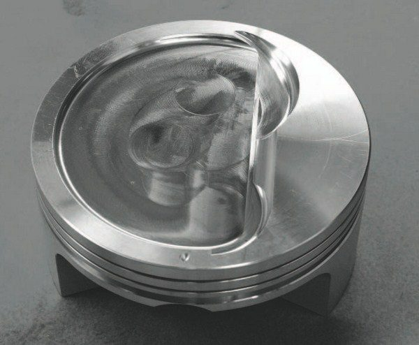 """A better piston selection for a supercharged or turbocharged street/strip LS engine is seen here in the """"D""""- shaped dish that provides a large, relatively efficient quench area. Quench is described as the squishing effect on the air charge as the piston reaches top dead center. The shape of the piston's dish helps squeeze air through the combustion chamber in a manner that generally helps even out the temperature throughout the chamber and reduces the chance for detonation. The depth of the dish affects the compression ratio."""