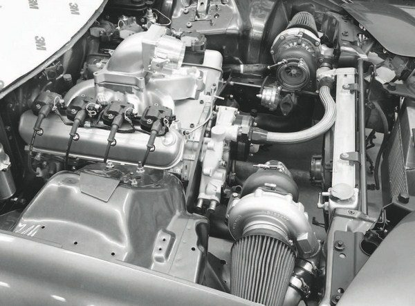 This photo shows a typical racing setup that uses a carbureted-style intake with an elbow designed to accept the injection system's throttle body. The aluminum intake also provides a measure of safety for high-boost engines, as the cast aluminum is less likely to shatter than the brittle nylon material of a production intake.