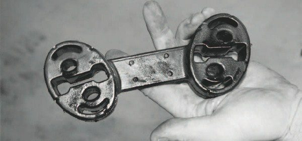 """The mufflers of many LS-powered vehicles are connected to the chassis via a """"dog bone""""-shaped connector. It must be pried off to enable removal of the exhaust system. This one looks wet because it was sprayed with WD-40 prior to removal to help slip it off the metal hanger that's welded to the chassis."""
