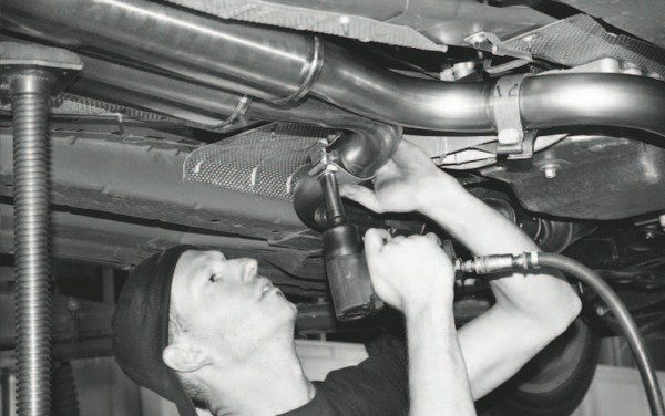 With the exhaust system in place, the fasteners are tightened completely. During the installation, they were only lightly torqued to allow easy adjustment and re-positioning. The last part of the exhaust installation involves the re-installation of the underbody cross member. The Corsa kit included a set of spacers to accommodate the resonators' thicker profile.