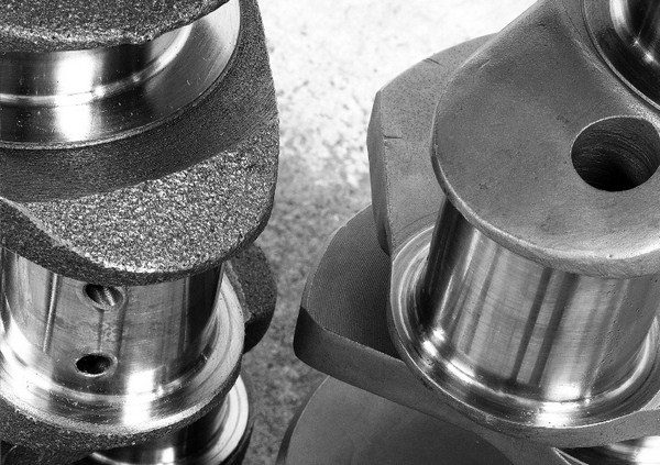 When comparing a cast crank (left) to a forged crank (right), it's obvious why the forged unit fetches a higher price tag. The cast crank's rough surface shows that very little finishing machine work is required, as the casting process yields a shape that closely resembles the end product. The forged crank's smoother and more refined appearance reveals the extensive machining operations required after the crank leaves the forging die.