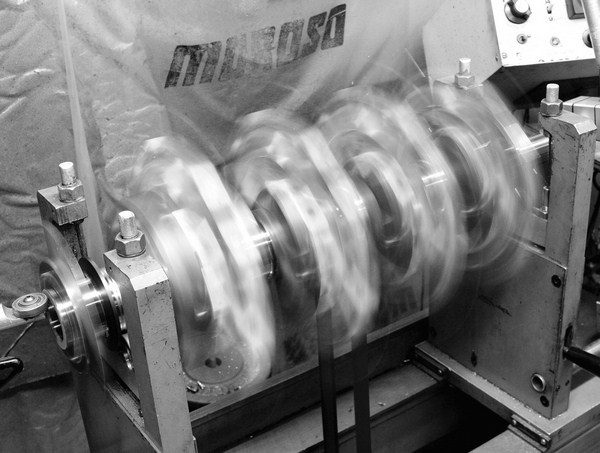 Balancing is performed on machines, such as the Sunnen DCB-750 digital balancer, which is the industry standard. Essentially a glorified tire balancer, the machine holds the crank in place on two stands, and then it spins the crank and bobweights up to 750 rpm. The stands on each side detect how much imbalance exits, and the machine calculates how much weight must be removed or added to correct it.